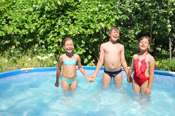 Two girls and a boy standing holding hands in a pool