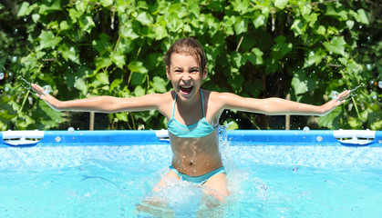 Cheerful girl in a blue swimsuit having fun at the pool