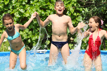 Three happy kids having fun in swimming pool