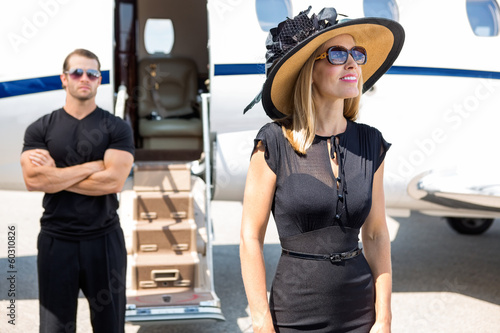 Happy Woman With Bodyguard And Private Jet In Background