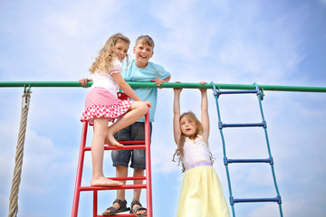 Three children at the top of playground equipment