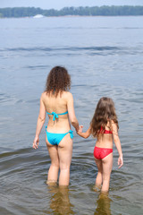 Back view of young mother and daughter