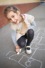 A smiling girl with a pigtail ends draw hopscotch