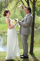 Beautiful bride and groom standing in a park holding hands
