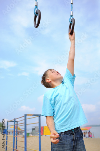 A boy engaged in sports rings on the playground
