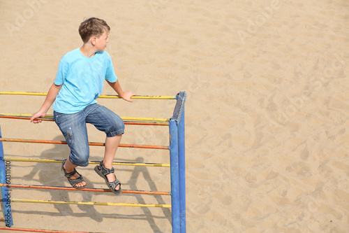 A boy sitting at the top of playground equipment
