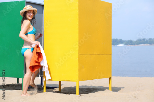 Woman comes in the changing cabin on the beach