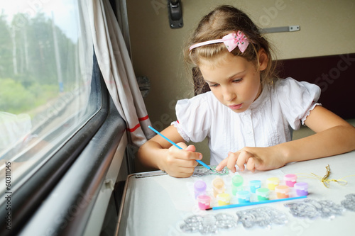Girl paints the picture while traveling in a train