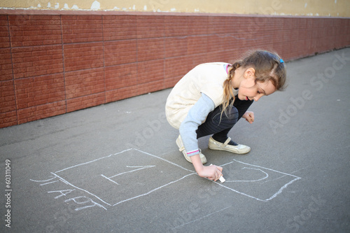 The girl begins to draw hopscotch on the pavement