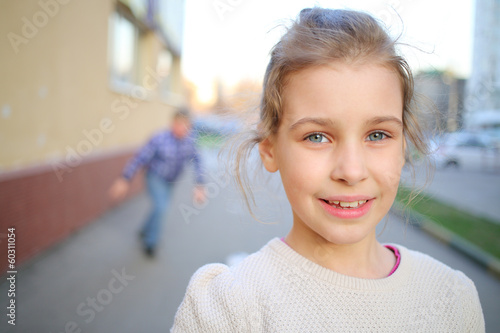 Outdoor portrait of a smiling girl in a white sweater
