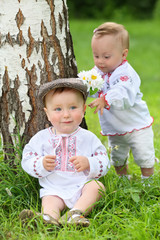 Little boy and girl in russian folk costumes near the birch