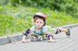 Little girl rides skateboard lying on it