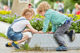 Little boy and girl play at edge of flowerbed on square