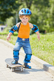 Little skateboarder stands on park alley with one his foot