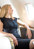 Rich Woman Looking Through Private Jet's Window