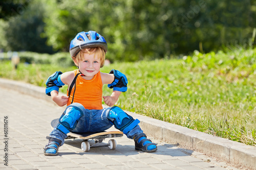 Little skateboarder sits on park alley on skateboard