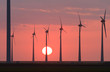 Row of wind turbines during a pink sunset.