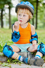 Little boy in protective equipment sits on curb of walkway