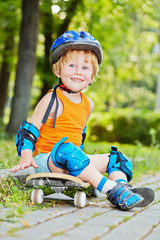 Smiling little boy in protective equipment sits on skateboard