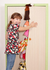 little girl trying to close messy closet