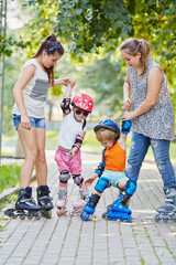 Two teen girls hold hands and help two kids beginners in rollers