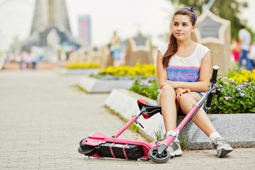 Young girl with electrical scooter sits on curb of flower bed