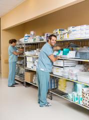 Nurses Arranging Stock On Shelves In Storage Room