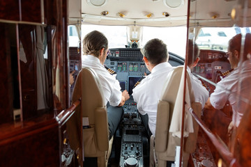 Pilots Operating Controls Of Private Jet