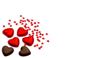 Heart-shaped chocolate pieces and small heart-shaped deco articl