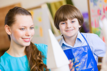 Children painting with teacher