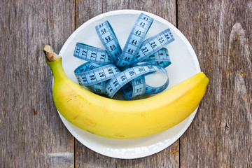 Banana and measurement tape in a plate