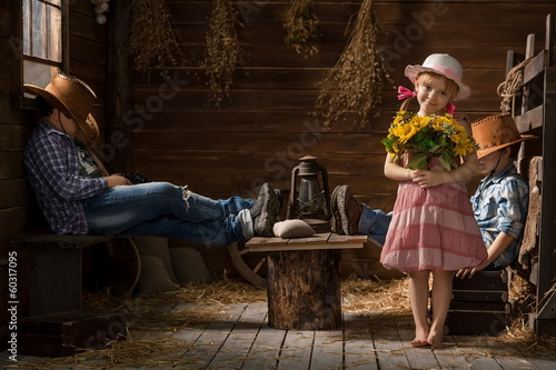 Three young children playing cowboys in the barn