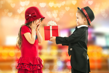 Little boy giving girl gift and his excited