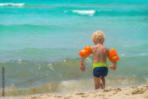 Small boy with water wings on sunny beach