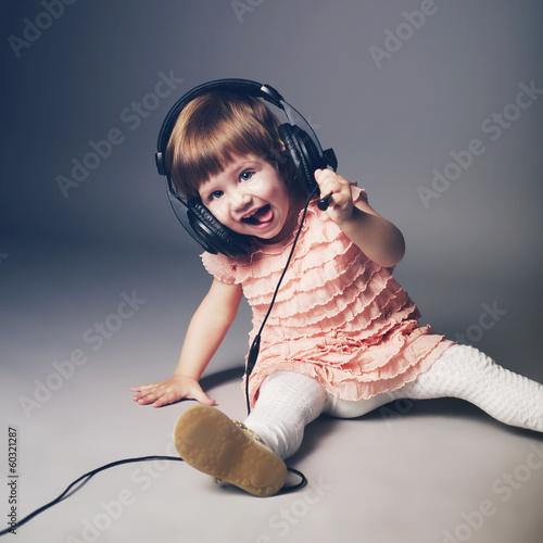 little happy girl with headphones at home