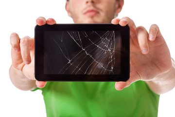 Young man holding broken tablet