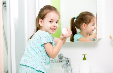 kid girl washing hands in bathroom