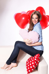 Portrait of a beautiful young woman holding a heart-shaped pillo