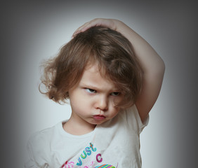 Angry kid on grey background. Closeup portrait