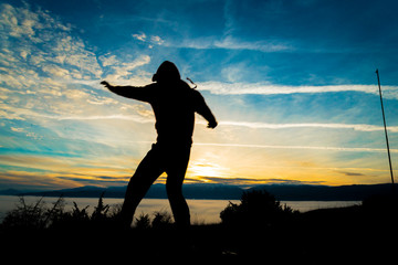 silhouete of a man jumping on sunset