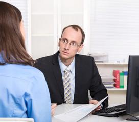 Berater einer Bank mit Kunde im Büro