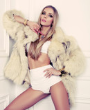 beautiful glamour model with blond hair in fur coat