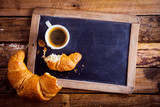 Coffee and a croissant on an old school slate