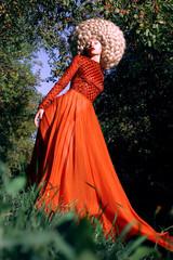Fantasy. Stylized Woman in Trendy Red Dress and Big Frizzy Wig