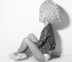 Vogue. Fanciful Woman Fashion Model in Creative Periwig sitting