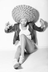 Creativity. Trendy Woman in Huge Fancy Wig sitting on Floor