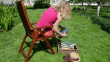 Woman sit on wooden chair and read old books in garden