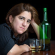 Portrait of a latin woman drinking alone isolated on black
