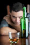 Sad drunk man staring at a glass of liquor