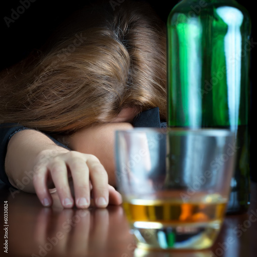 Drunk alcoholic woman sleeping on a table